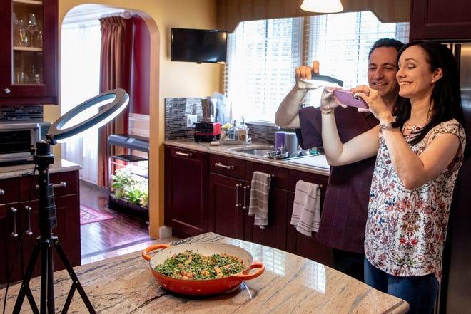 Food lovers Kaitlin and Greg Dalakian love a good meal. Greg Dalakian holds a light while Kaitlin Dalakian takes photos of food in their Boonton home.